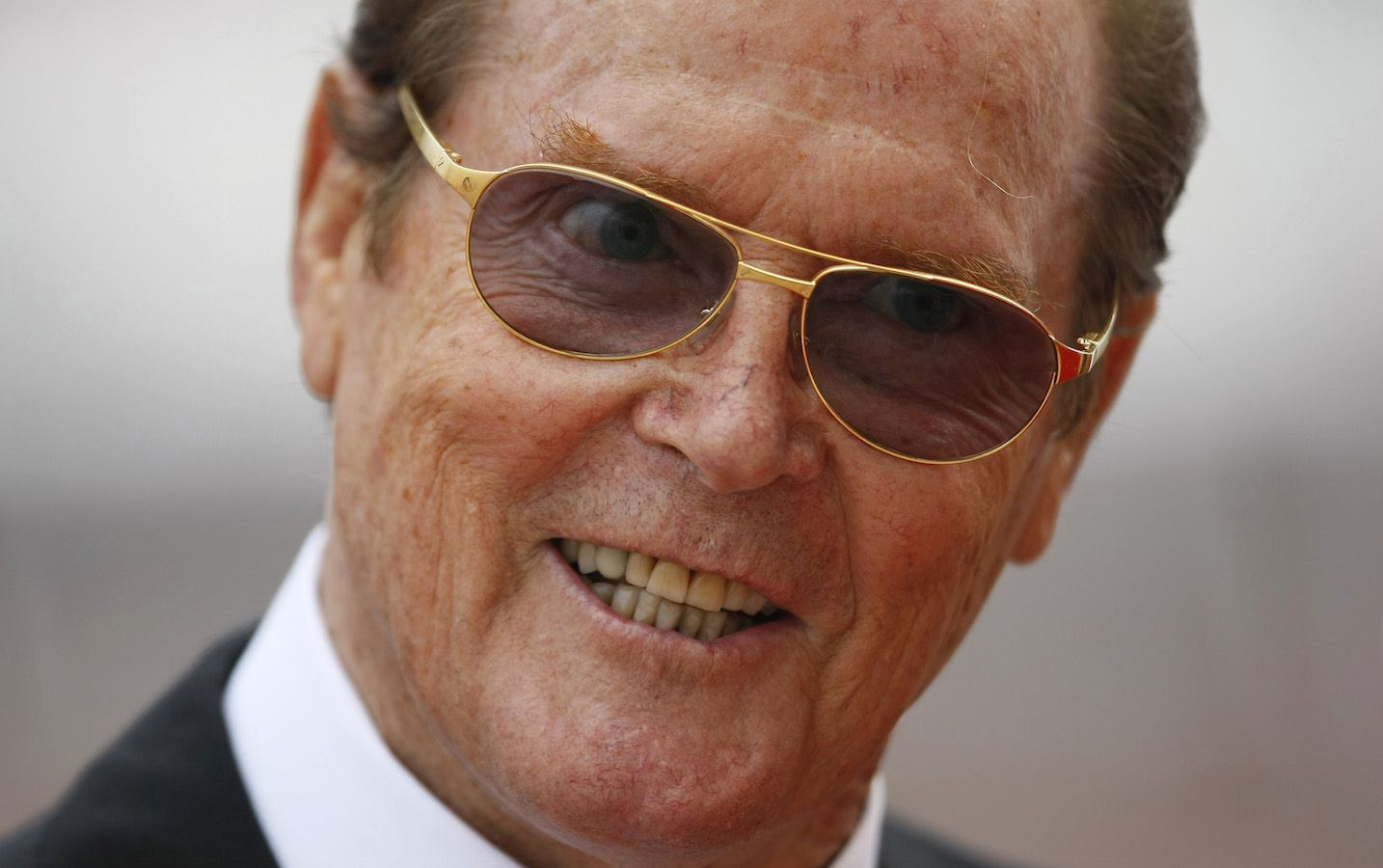 British actor Sir Roger Moore arrives at the Place du Palais to attend the religious wedding ceremony for Monaco's Prince Albert II and Princess Charlene at the Palace in Monaco July 2, 2011. REUTERS/Michel Spingler/Pool (MONACO - TAGS: ROYALS ENTERTAINMENT HEADSHOT) (MONACO ROYAL WEDDING) - RTR2ODYB