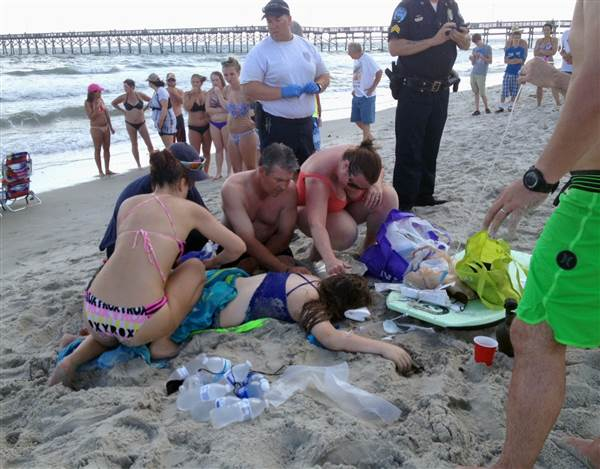 Emergency responders assist a teenage girl Sunday after a shark attack at Oak Island, North Carolina. Steve Bouser / AP